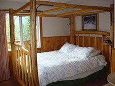 Upper Main Lodge bedroom with a canopy log bed